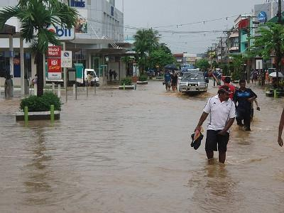Fiji citizens wading through brown flood water.