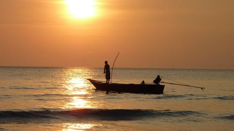 Man fishing in boat at sunset