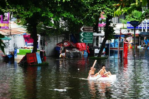 Boys rowing boat in flooded Bangkok street